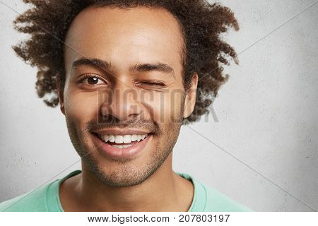 Close Up Portrait Of Dark Skinned Afro American Guy With Positive Expression, Blinks Eye And Smiles