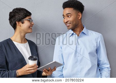 Sophisticated Mixed Race Female And Male Colleagues Have Conversation Together, Discuss Future Meeti