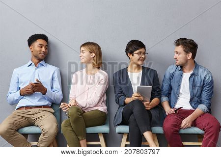 Horizontal Portrait Of People Sit In Queue, Have Pleasant Conversation With Each Other, Share Ideas