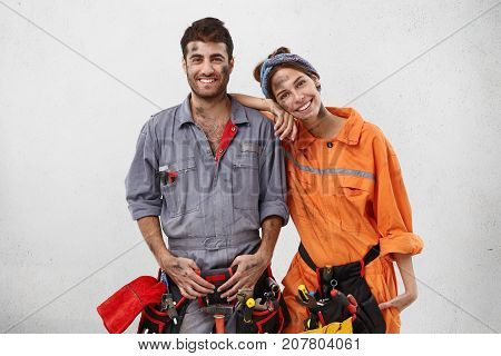 Smiling Dirty Woman Leans On Shoulder Of Man Mechanic, Helps Him To Repair Car On Work Station, Rejo