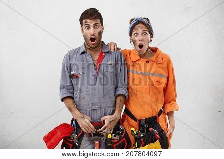 Astonished Female And Male Technicians Look At Camera With Widely Opened Mouth, Realize That They Fo