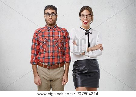 Best Friends Stand Next To Each Other: Unshaven Puzzled Man In Glasses And Checkered Shirt And Beaut