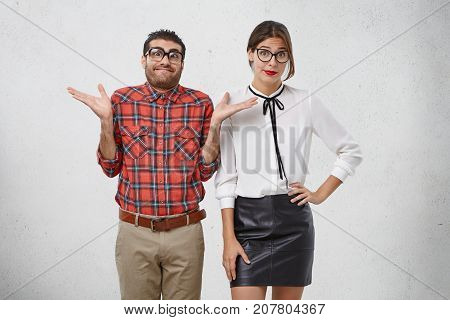 Ridiculous Man And Woman Dressed Formally, Wear Spectacles, Shrug Shoulders In Bewilderment, Don`t K