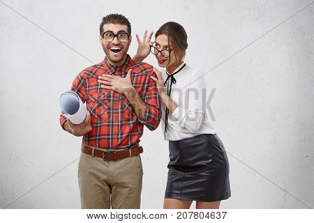 Brunette Pleasant Looking Woman Looks Attentively Through Spectacles At Her Boyfriend Who Is Overjoy