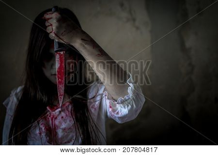 Ghost woman or zombie hold knife for kill with blood violence in house of ruin nightmare horror of scary fear on hell is monster devil in halloween festival copy space the right.