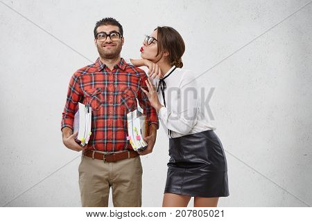 Cute Attractive Female Dressed Formally, Going To Kiss Boyfriend Who Holds Piles Of Books, Helps Her