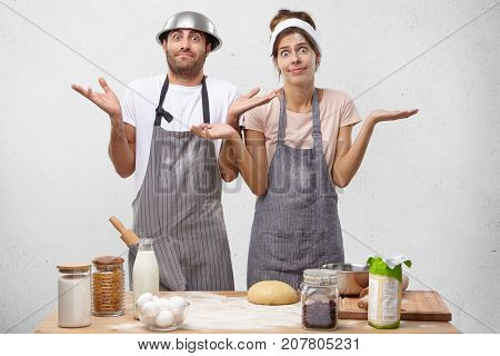 Portrait Of Emotional Clueless Young Couple Male And Female Learning How To Cook, Preparing Food Tog