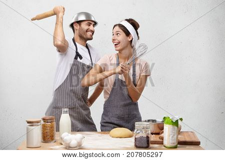 Happy Female And Male Foolish At Kitchen, Fight With Whisk And Rolling Pin, Have Glad Expressions. O