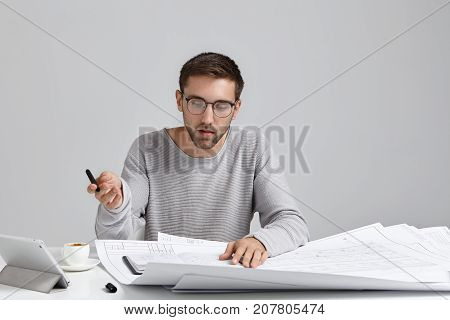 Serious Concentrated Male Designer Wears Loose Sweater And Round Glasses, Looks Attentively At Sketc