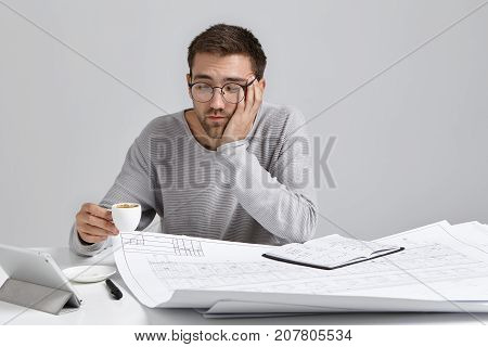 Sleepy Man Drinks Coffee As Feels Tired, Works All Day At Blueprints, Has Fatigue Expression, Being