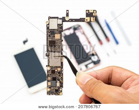 Close-up of technician hand clamping smartphone logic board on blurred smartphone component background
