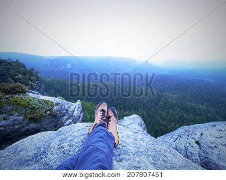 Detail Of  Hiker Legs In Black Orange Hiking Boots On Mountain Summit. Feet In Trekking Shoes