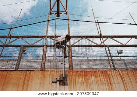 Big street surveillance camera on wall of old prison with rusty streaks and grid barbed wire fence under blue sky with clouds.