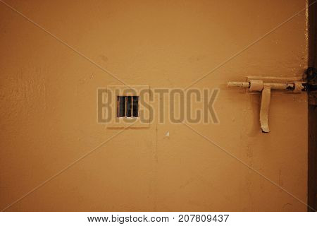 Close up view of yellow metallic door with bolt lock and little grate in old prison.