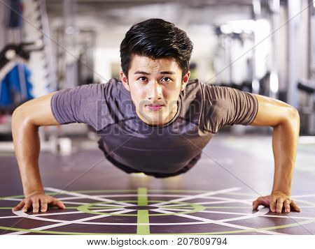 young asian adult man exercising in gym doing pushups frontal view.