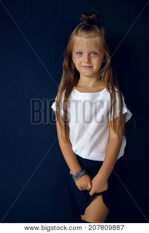 girl in white shirt posing in the studio against the wall