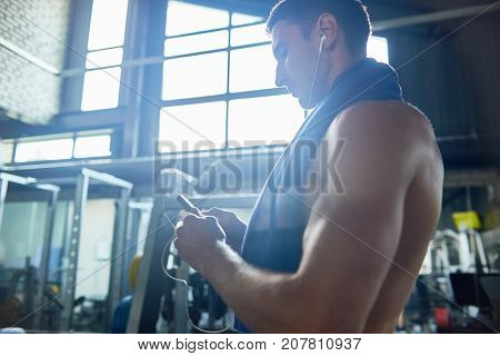 Getting ready for intensive workout: handsome young man in headphones turning on mp3 player while standing at spacious gym, profile view