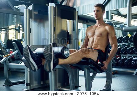 Muscular young man with naked torso doing exercise on leg extension machine while having intensive training at modern gym