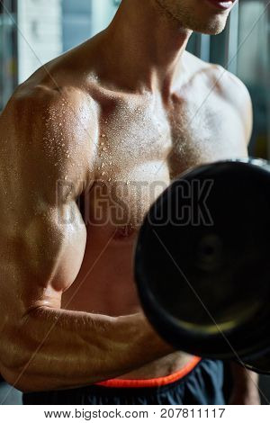 Close-up shot of sweaty muscular man pumping up muscles with dumbbell while having intensive training at gym