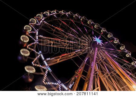 Ferris wheel at night with a motion blur and lens flares at the christmas market
