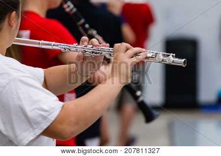 the hands of a musician playing a flute