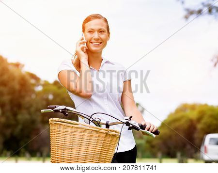 Beautiful young blond woman with bike in park talking over phone