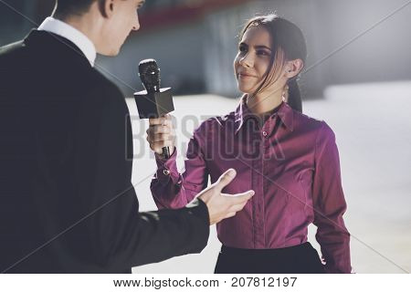 TV reporter at work. On a clear day, a girl interviews a man in a suit