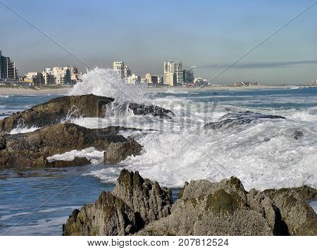 WINTER SEASCAPE, WITH WAVES CRASHING OVER SOME HUGE BOULDERS AND SPRAYING UP INTO THE AIR