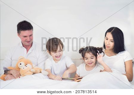 Father Mother Brothers and sister read a bedtime story togather on the bed in bedroom kid child family study education and home work concept