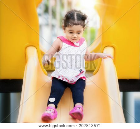 Asian girl play a slider in Playground in her school kid and fun concept