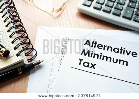 Alternative Minimum Tax (AMT)and  calculator on a desk.
