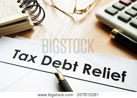 Papers with title tax debt relief on a desk.