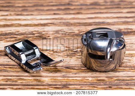 two metal parts from a sewing machine on a wooden table