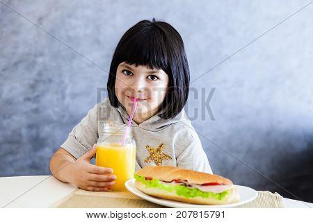 Cute Black Hair Little Girl Having Breakfast And Drinking Orange Juice