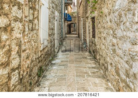 Old Town Street Budva, Montenegro. The first mention of this city - more than 26 centuries ago. We see ancient houses, a very narrow street, cafes, shops.