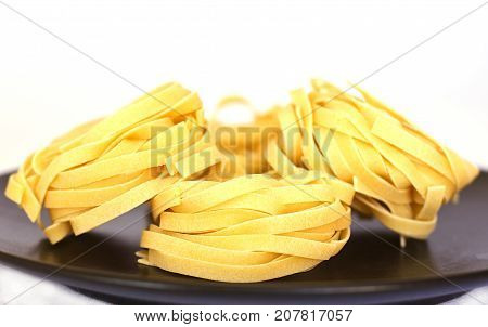 Uncooked Tagliatelle On A Black Ceramic Plate. Isolated