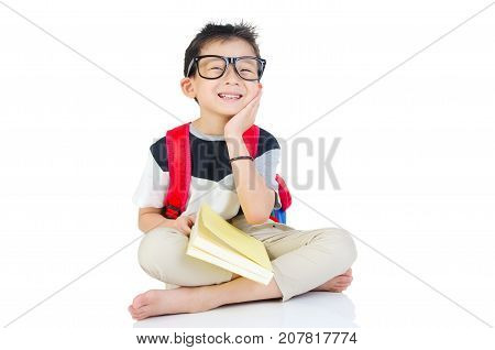 Asian preschool boy with schoolbag and books sitting on the floor