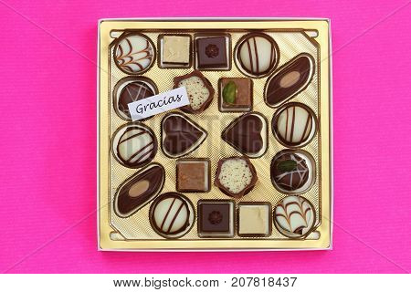Gracias (which means thank you in Spanish) card with box of assorted chocolates on pink background