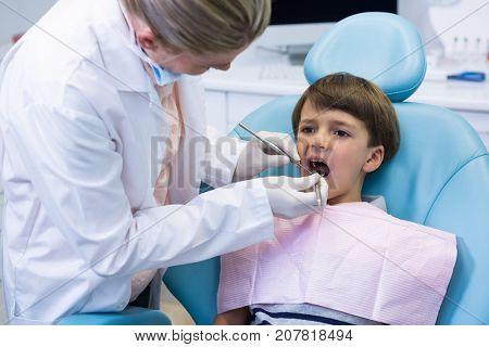 Boy receiving dental treatment by dentist at medical clinic