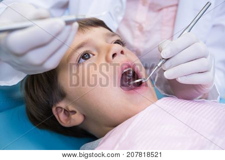 Close up of dentist holding equipment while examining boy at medical clinic