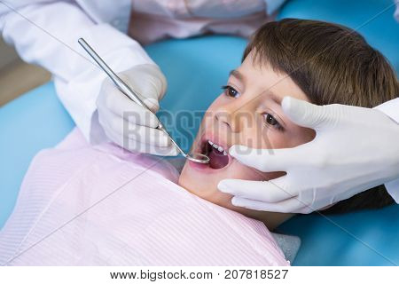 Cropped image of dentist holding equipment while examining boy at medical clinic