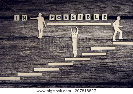 Conceptual possible - impossible letter tiles sign with person walking upstairs wooden background.