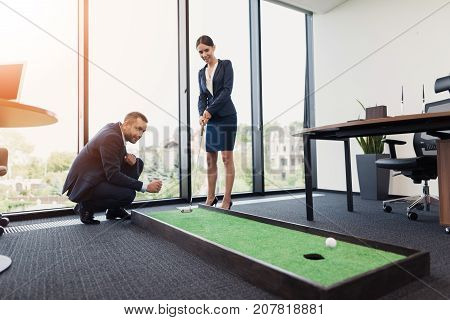 The subordinate in a strict business suit put out a golf ball, and his boss, the business lady made an excellent kick with the club
