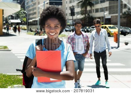 Laughing african american female student in the city in the summer