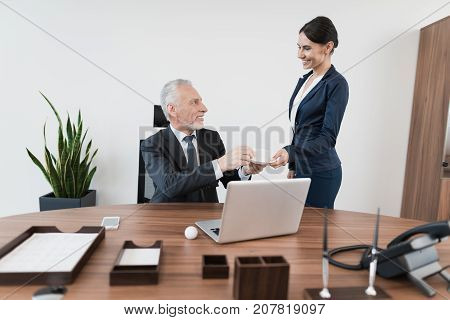 The secretary's woman brought her representative in a dark suit of coffee. He sits at his desk, behind him is an open laptop behind which he works