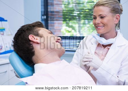 Happy patient looking at dentist while sitting on chair in medical clinic