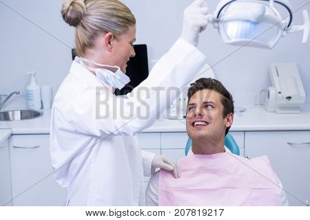 Side view of dentist adjusting electric light while patient sitting on chair at clinic