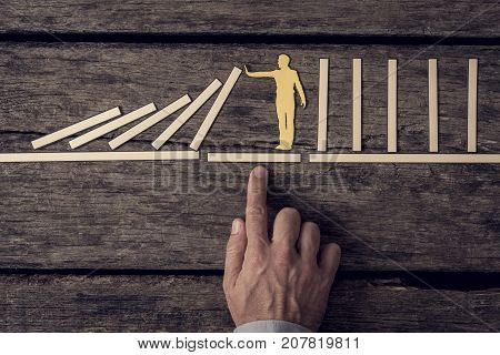 Businessman demonstrating stopping the domino effect using paper cut outs supported by his hands toned retro effect.