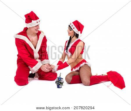Happy young couple wearing santa claus clothes posing against isolated white background in full length.