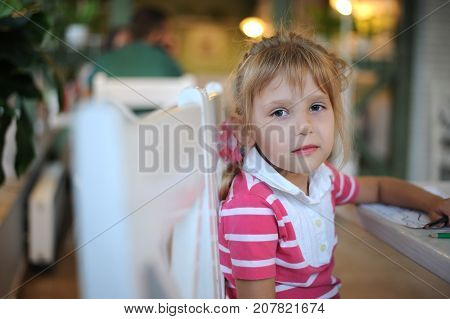 Beautiful girl in a cafe waiting for the ordered dessert. Cafe furnished with white furniture. A girl dressed in white jeans and pink T-shirt. A girl 6-8 years